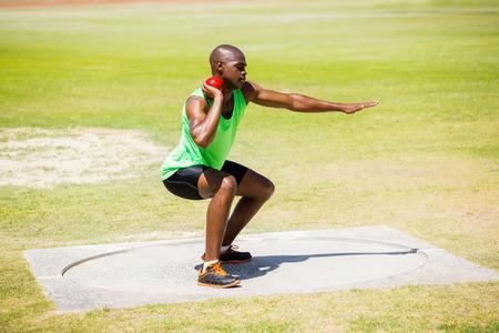 shot put: Male athlete preparing to throw shot put ball in stadium Foto de archivo