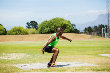 put: Male athlete preparing to throw shot put ball in stadium Stock Photo