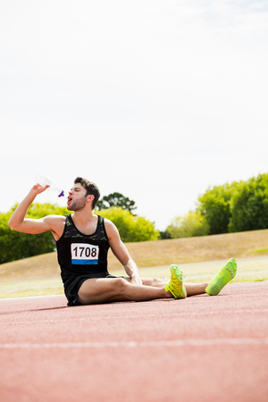 tomando refresco: Tired athlete sitting on the running track and drinking water on a sunny day Foto de archivo