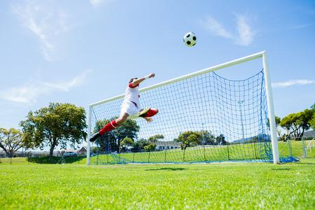scoring: Football player scoring a goal while playing soccer Stock Photo