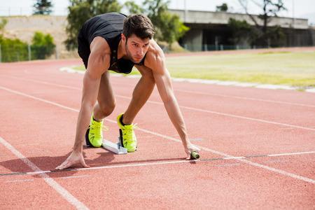 hombres corriendo: Atleta listo para iniciar la carrera de relevos en la pista de atletismo Foto de archivo