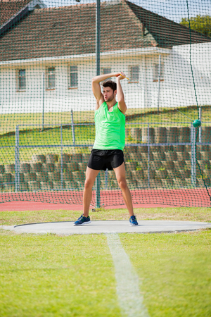 performing: Athlete performing a hammer throw in stadium Stock Photo