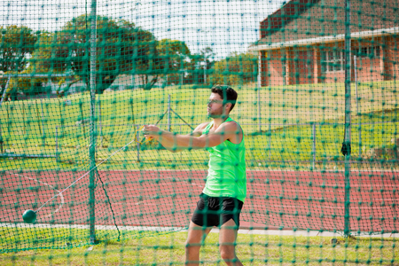 hammer throw: Athlete performing a hammer throw in stadium Stock Photo