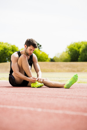 shoe laces: Athlete tying his shoe laces on running track on a sunny day Stock Photo