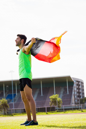 german flag: Athlete posing with german flag after victory in stadium Stock Photo