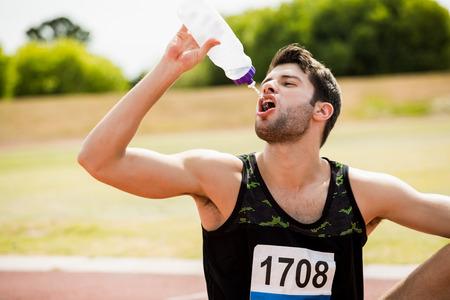 tomando refresco: atleta cansado que se sienta en la pista de atletismo y el agua potable en un día soleado