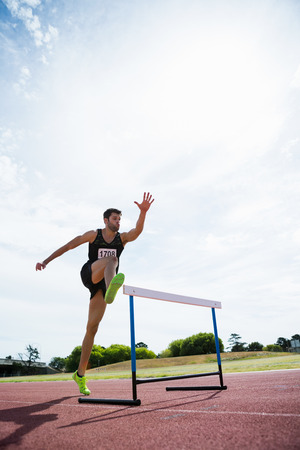 hurdle: Athlete jumping above the hurdle during the race