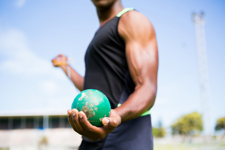 hammer throw: Mid section of athlete holding hammer throw in stadium