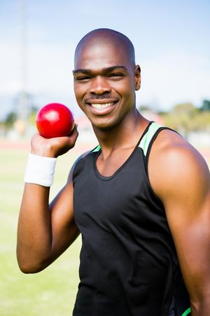 shot put: atleta masculino que se prepara para lanzar bola de tiro puesto en estadio
