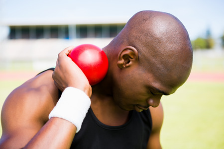 athleticism: Male athlete holding shot put ball in stadium Stock Photo