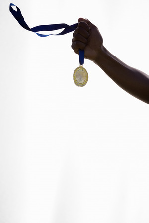 cut the competition: Hand of athlete holding gold medal on white background
