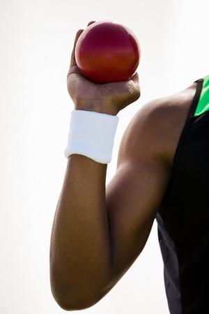 lanzamiento de bala: Atleta de sexo masculino que sostiene lanzamiento de bala pelota en el estadio