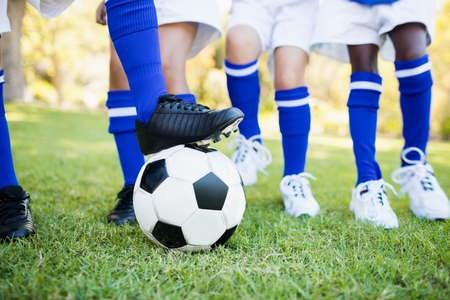 football boots: Close up view of balloon under football boots with children playing in park