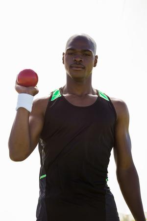 lanzamiento de bala: Retrato de atleta masculino celebración de lanzamiento de poner la bola en el estadio