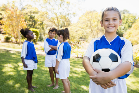 bare feet boys: Girl posing with her soccer team in the background in park Stock Photo