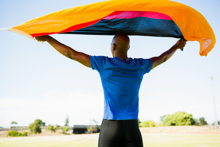german flag: Rear view of athlete posing with german flag after victory in stadium