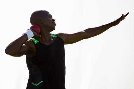lanzamiento de bala: atleta masculino que se prepara para lanzar bola de tiro poner en el fondo blanco Foto de archivo