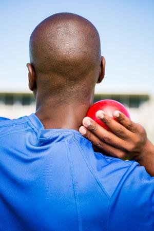 lanzamiento de bala: Vista trasera de atleta masculino que se prepara para lanzar bola de tiro puesto en estadio