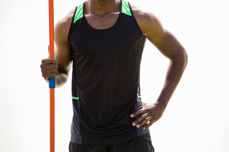 mid section: Mid section of athlete standing with javelin in stadium Stock Photo