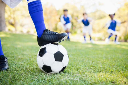football boots: Close up view of balloon under football boots against children playing background in park