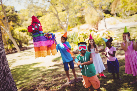 Little boy is going to broke a pinata for his birthday in a park Stock Photo