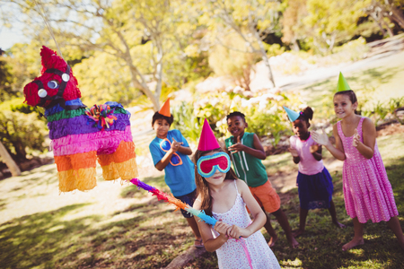 pinata: Little girl is going to broke the pinata for their birthday in a park