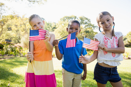 weekend activity: Happy children showing usa flag at park Stock Photo