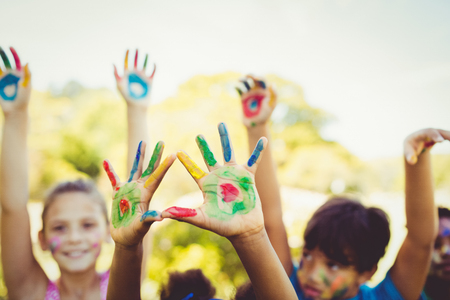 fond of children: Portrait of cute children with make up having coloured hands in a park