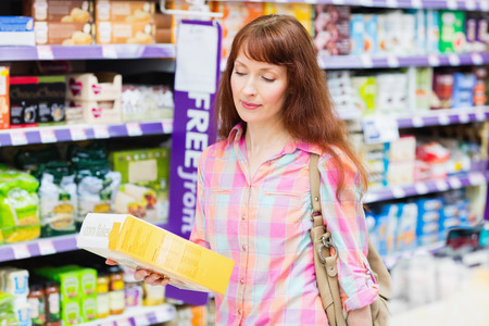 customer facing: Thoughtful woman choosing a product at supermarket