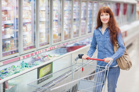 customer facing: Smiling woman pushing trolley in aisle at supermarket Stock Photo