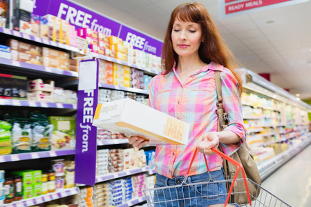 customer facing: Portrait of woman putting product in shopping basket at supermarket