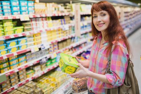 customer facing: Woman smiling at camera while holding product at supermarket