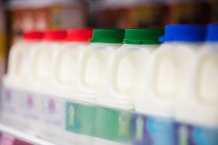 store shelf: Milk bottles tidied in shelf at grocery store Stock Photo