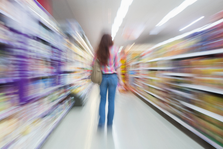 weekend activities: Rear view of woman standing in aisle with blurred effects at supermarket Stock Photo