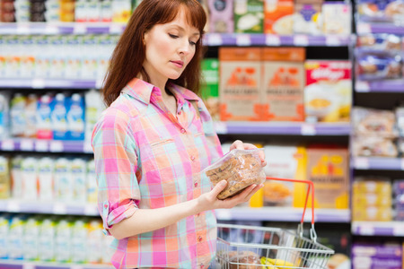customer facing: Concentrated woman choosing carefully a product at supermarket