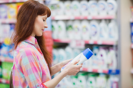 profile view: Profile view of woman choosing detergent at supermarket
