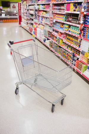 weekend activities: Empty trolley in the aisle of a supermarket Stock Photo