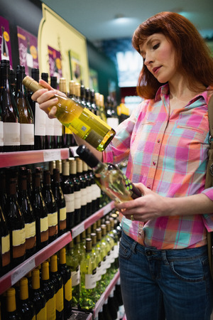 dudando: Woman hesitating between two bottles of wine in supermarket