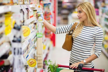 retail shopping: Woman choosing a product in an aisle