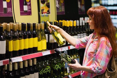 hesitating: Consumer hesitating between two bottles of wine in supermarket Stock Photo