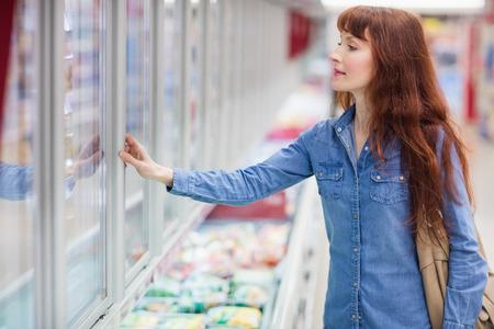 alimentos congelados: Mujer concentrada que la compra de alimentos congelados en el supermercado