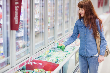 negocios comida: Woman buying vegetables in frozen section in supermarket