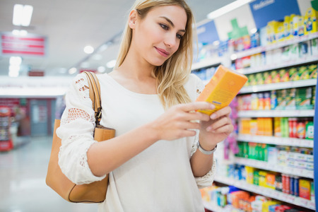 customer facing: Serious woman buying a product in a supermarket