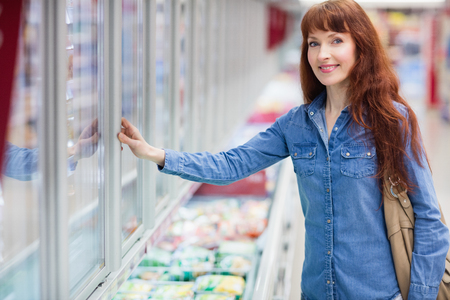 customer facing: Woman smiling at camera while doing grocery shopping in frozen section