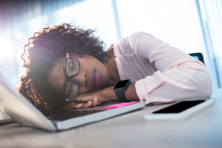 at her desk: Businesswoman sleeping on her desk at office
