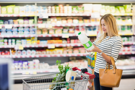 Woman looking at a product in a supermarket