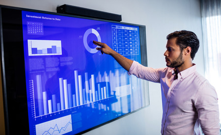 Businessman analyzing data with a touch screen in office 스톡 콘텐츠