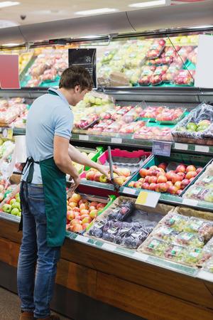 shop assistant: Shop assistant arranging shelves in a grocery shop Stock Photo