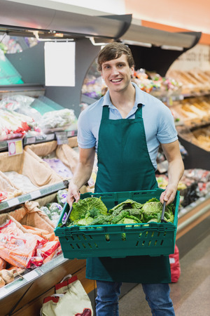 grocer: Portrait of man grocer holding a crate of vegetables on a grocery
