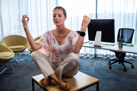 corporate women: Businesswoman doing yoga with hands in the air at office